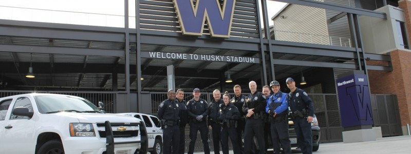Group of UW officers smiling in front of Husky Stadium.