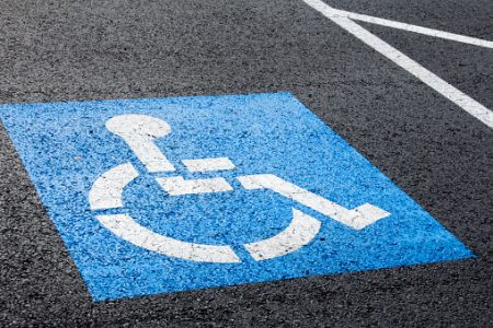 Disabled parking sign on pavement.